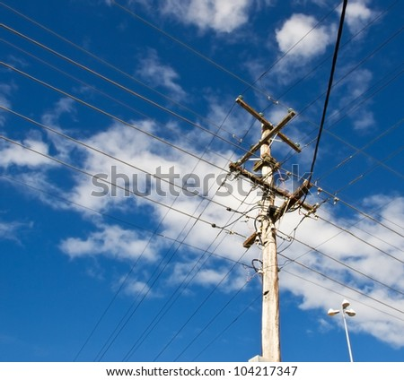 power lines for australian power pole electricity grid against cloudy blue sky - stock photo