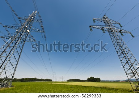 Power lines in a summer landscape with clear sky - stock photo