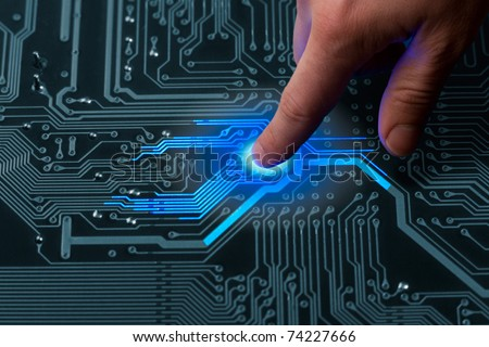 power mans finger is charging passive circuit board with blue energy - stock photo