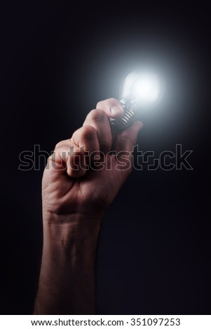 Power of creative thinking, concept of new ideas, innovation and creativity with hand holding light bulb, retro toned image, selective focus. - stock photo