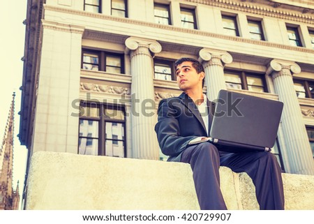 Power of Modern Technology. East Indian American college student traveling, studying in New York, sitting on street outside office building, working on laptop computer. Instagram filtered effect.  - stock photo