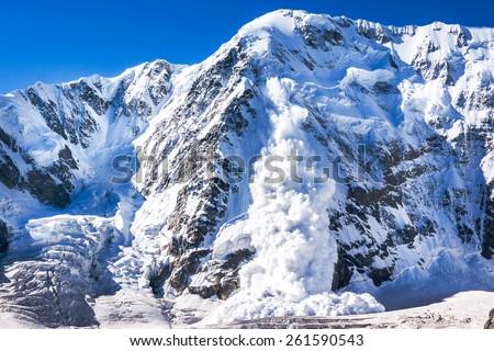 Power of nature. Real huge avalanche comes from a big mountain (Shkhara, 5,193 m), Caucasus, Kabardino-Balkaria, Bezengi region, Russia - stock photo