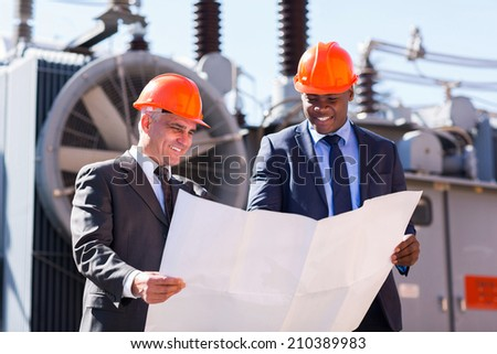 power plant managers holding blueprint at substation - stock photo