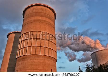 Power plant smoke chimney sunset - stock photo