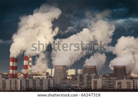 Power plant smokestacks emitting smoke over urban cityscape - stock photo