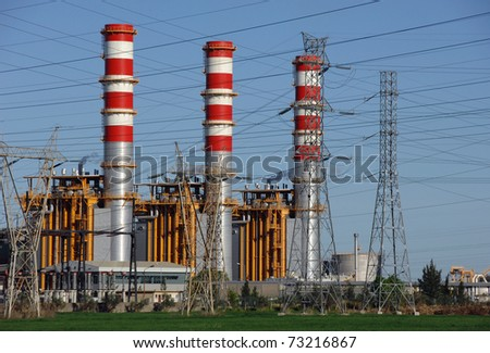 Power plant smokestacks,  emitting steam - stock photo