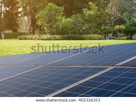 Power plant using renewable solar energy with sunlight over green garden background - stock photo