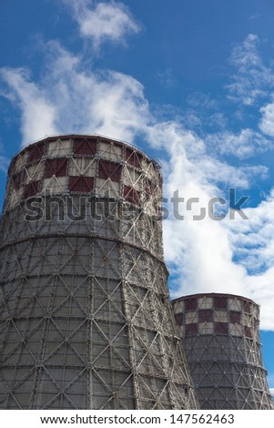 Power plant with huge cooling towers against blue sky - stock photo