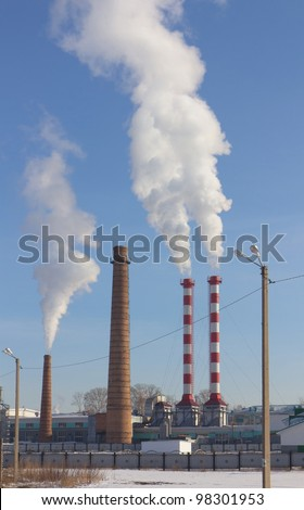 Power plant with pipes and smoke - stock photo
