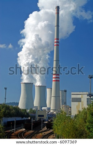 Power plant with supply coal wagons and clouds of white vapour - stock photo