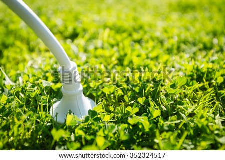 Power plug connected to the green source of energy - stock photo