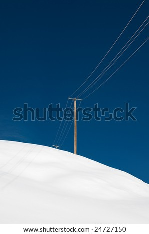 Power pole and wire on a snowy hill - stock photo