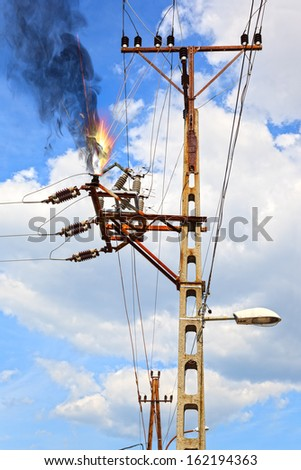 Power pylon - overloaded electrical circuit causing electrical short. - stock photo