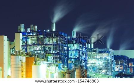power station at night with smoke  - stock photo
