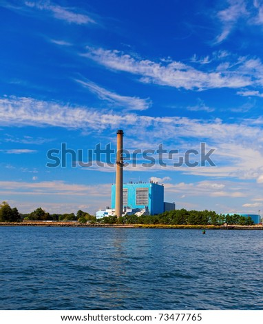 Power station by the edge of the ocean with blue sky - stock photo