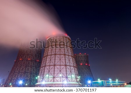 Power station with a steam cloud blown by the wind in a cold starry winter night - stock photo