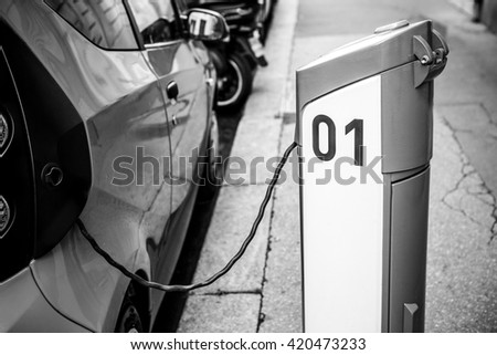 Power supply for electric car charging. Electric car charging station. Close up of the power supply plugged into an electric car being charged. Black-white photo.  - stock photo