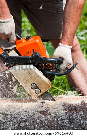 Power tool. Lumberjack cutting the log of wood with petrol chainsaw - stock photo