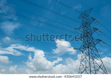 Power tower against clouds and blue sky. - stock photo