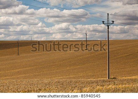 Power-transmission poles on the empty barley field in summer - stock photo