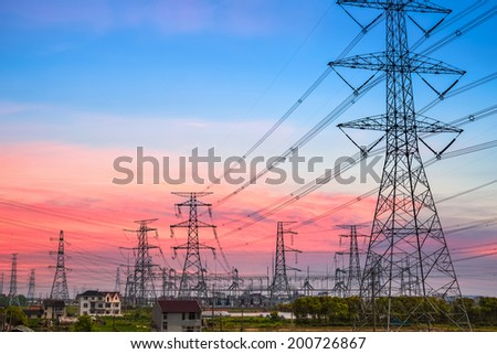 power transmission tower silhouetted against the sunset glow  - stock photo