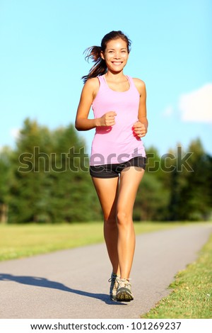 Power walking woman training in park. Beautiful sporty fitness model during outdoor workout. Mixed race Asian Chinese / Caucasian girl. - stock photo