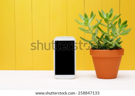 Powered Off Modern Mobile Phone Standing Beside Green Plant on a Pot with Yellow Wooden Wall Background - stock photo