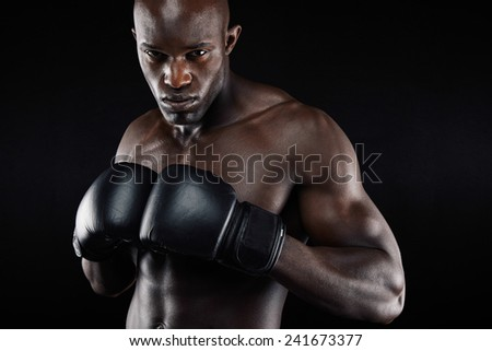 Powerful boxer posing and looking tough against black background. African muscular man practicing boxing workout. - stock photo