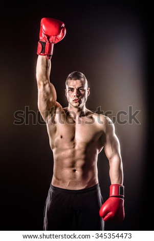 powerful boxer raising gloves after victory - stock photo