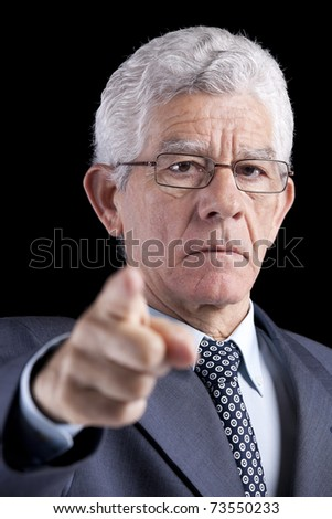 Powerful businessman pointing to you (isolated on black) - stock photo