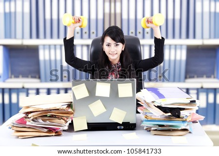 Powerful businesswoman exercising with dumbbells at office - stock photo