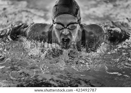 Powerful butterfly stroke swimming. Frozen motion, black and white - stock photo