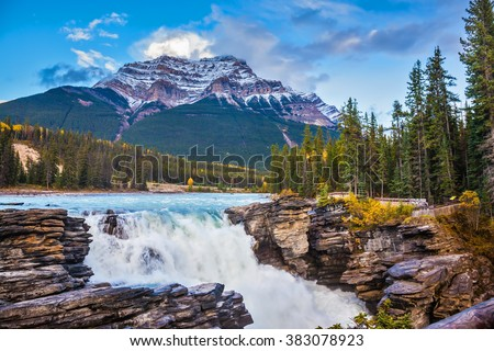 Powerful picturesque waterfall Athabasca. Pyramidal mountain covered with the first snow. Canada, Jasper National Park - stock photo