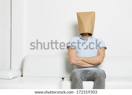 Powerful self confident man with head covered by a blank paper bag sitting on sofa with arms crossed,  empty space for text, on white background. - stock photo