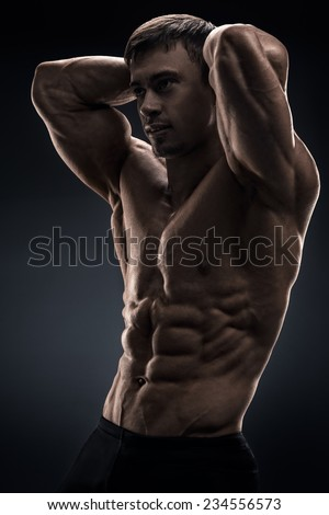 Powerful shirtless male bodybuilder posing over black background. Studio shot on black background. - stock photo