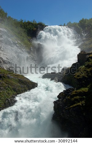Powerful waterfall from Norway glacier - stock photo