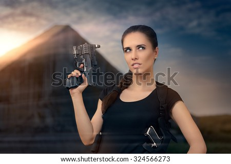 Powerful Woman Holding Gun Action Movie Style - Portrait of a girl in a heroine cosplay  accessorized costume   - stock photo
