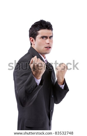 Powerful young businessman very angry with you (isolated on gray) - stock photo