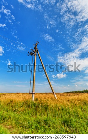 Powerline beneath blue sky with cumulus clouds - stock photo