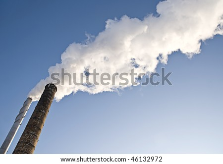 Powerplants polluting air, large smoke clouds from towers - stock photo