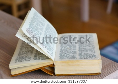 POZNAN, POLAND - AUGUST 29, 2015: Dictionary in Polish and English language on wooden table - stock photo