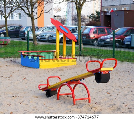 POZNAN, POLAND - DECEMBER 27, 2015: Seesaw and sand box at a play ground by apartment blocks - stock photo