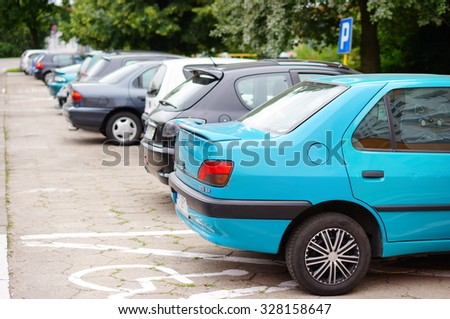 POZNAN, POLAND - JUNE 19, 2014: Row of parked cars on a parking lot at the Osiedle Piastowskie area - stock photo