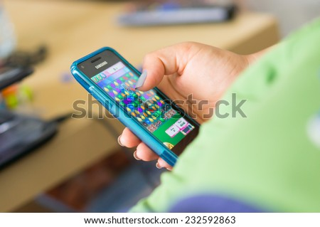 POZNAN, POLAND - MAY 08, 2014: Person playing Candy Crush Saga game on a smartphone - stock photo