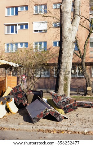 POZNAN, POLAND - NOVEMBER 08, 2015: Old furniture pieces next to a trash area by a apartment building - stock photo