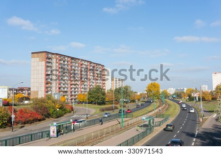 POZNAN, POLAND - OCTOBER 24, 2015: Cars driving on a road next to apartment buildings - stock photo