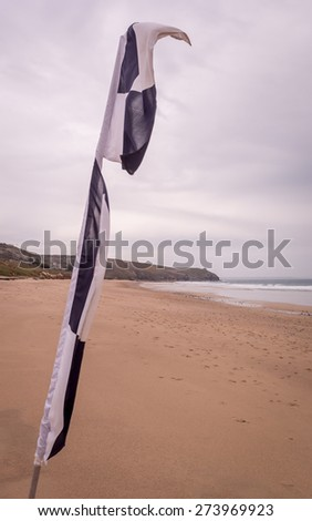 Praa sand in cornwall england uk. Stunning coastline and sandy beaches. Life saving black and white flag for surfers - stock photo