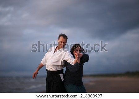 Practicing Japanese martial arts on the beach; woman doing self-defense technique - stock photo