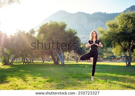 Practicing yoga in the morning, with trees, mountains and sun ray in the background. Attractive young caucasian woman standing in yoga pose on the grass. - stock photo