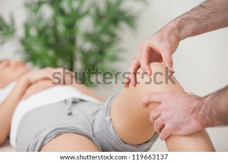 Practitioner using his fingers to massage a knee in a room - stock photo